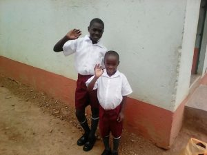 The 2 boys mentioned above happy and dressed in their new school uniforms